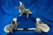 La férula consiste en una barra (de longitud igual a la distancia entre los hombros del bebé) a la que están unidas en 70 grados de rotación externa unas botitas altas abiertas por la parte anterior que dejan los dedos descubiertos y libres para su dorsiflexion